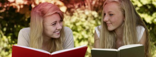 Kuva kahdesta tytöstä lukemassa kirjoja. Kuva kuvastaa kaikkia myyttejä, joita liitetään kuukautisiin.