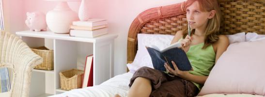 Kuva nuoresta tytöstä istumassa sängyllä kirjan kanssa. Kuva kuvastaa niitä monia kysymyksiä nuorilla on ensimmäisistä kuukautisista.