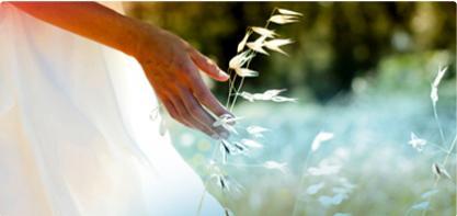 Kuva naisesta valkoisessa mekossa pellolla. Kuva kuvastaa o.b. tamponeiden ekologista kestävyyttä ja luonnonsuojelemista.